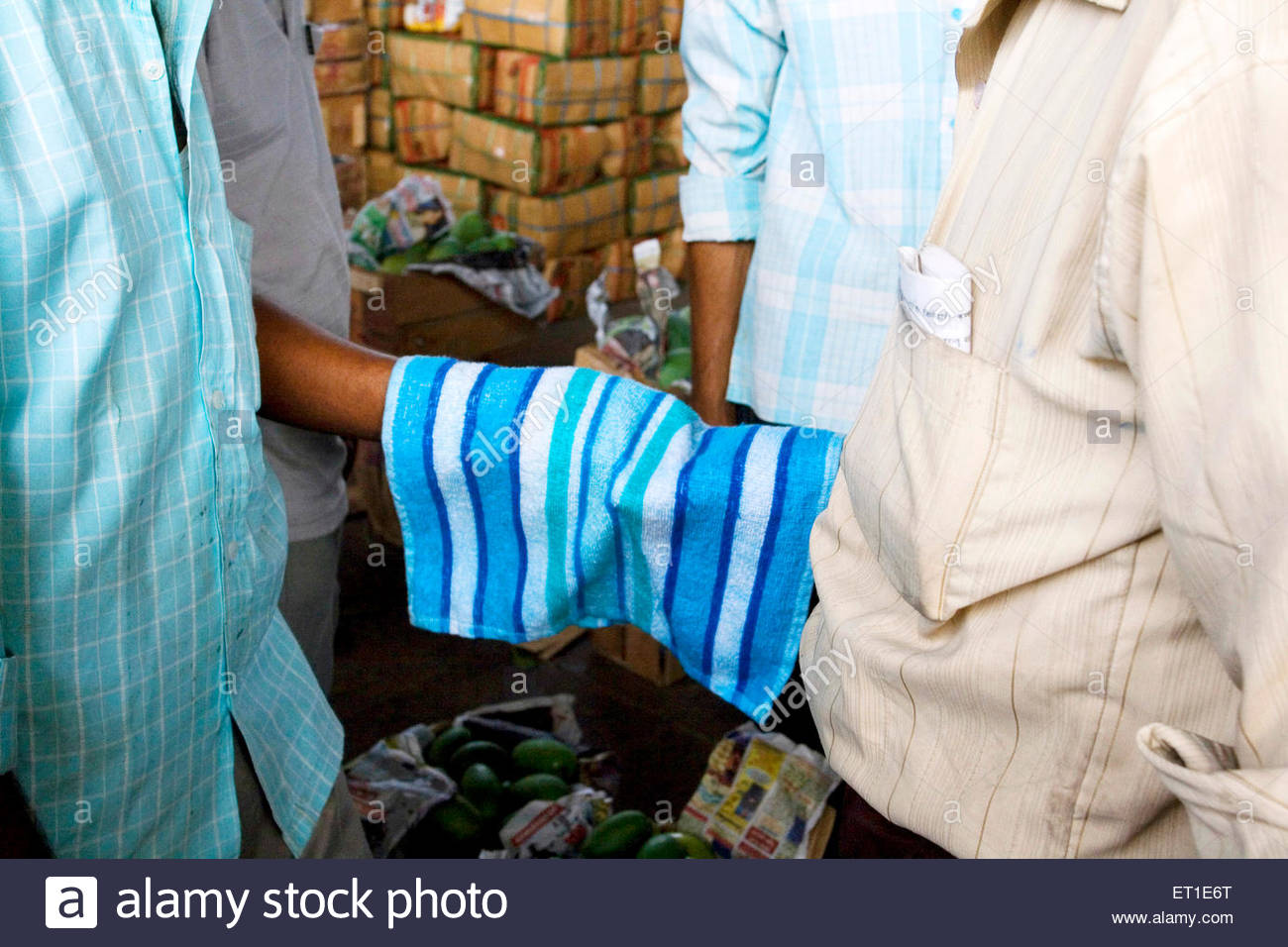 Secret auction system using hand hidden by towel ; New Delhi ; India - Stock Image