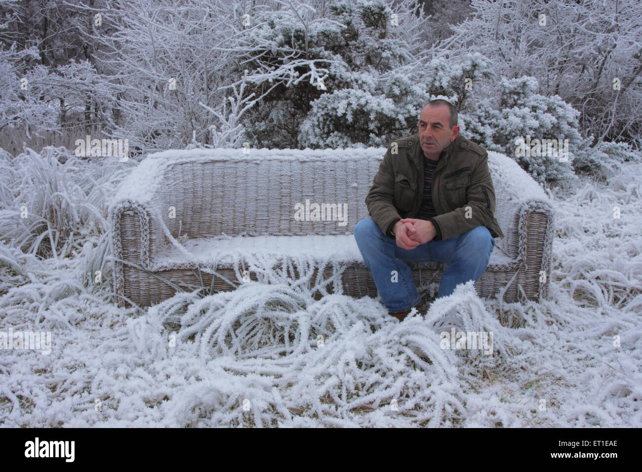 Man seated on abandoned, dumped frost covered settee in winter. - Stock Image