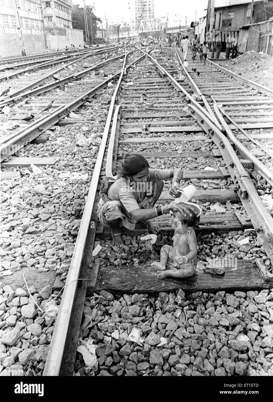 Mother bathing her son on railway tracks at Wadala ; Bombay Mumbai ; Maharashtra ; India NO MR - Stock Image