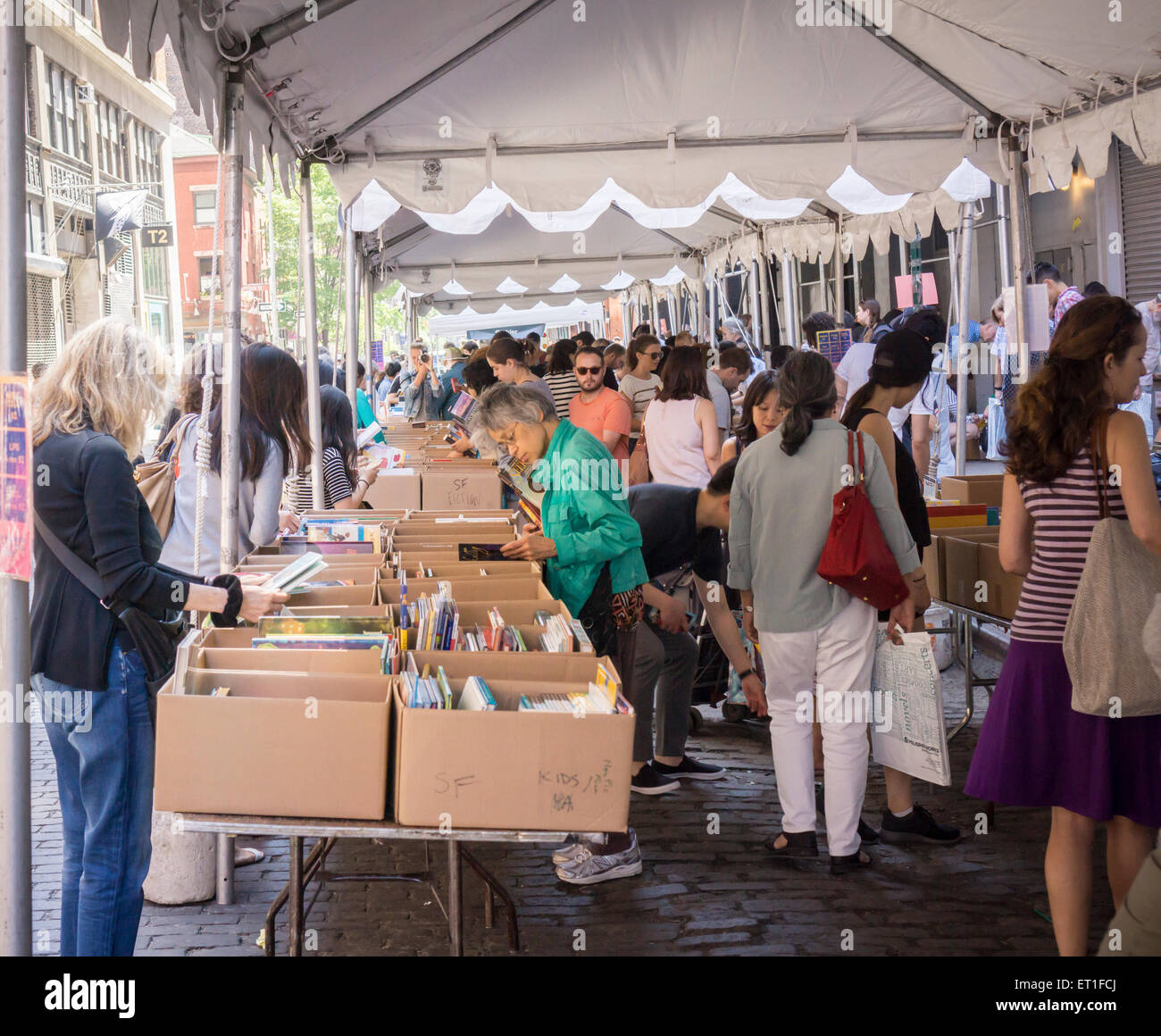 Shoppers search for bargains amidst the chaos of the Housing Works street fair on Crosby Streetin the New York neighborhood Stock Photo
