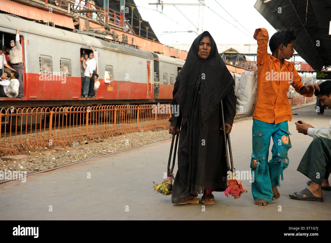 Handicap muslim lady with crutches on platform ; India NO MR - Stock Image