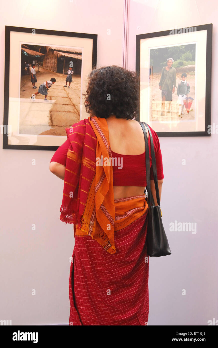 Lady watching photographs ; New Delhi ; India - Stock Image