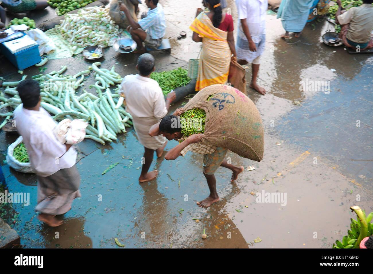 Man carrying jute sack in market ; Thanjavur  ; Tamil Nadu ; India - Stock Image