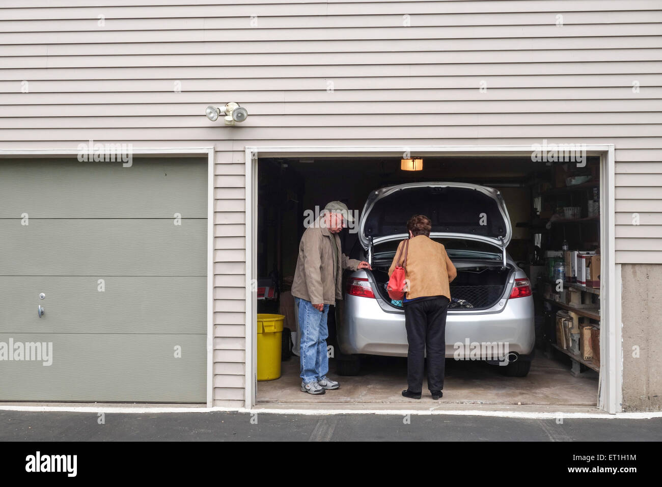 garage door inside. Senior Couple Leaving, Garage Door With Car Parked Inside, American Style Wooden House, USA. Inside P