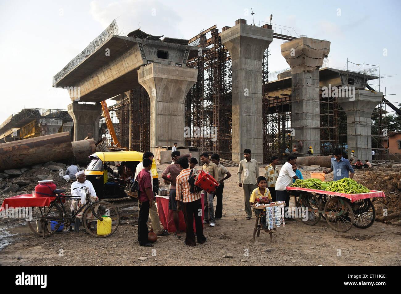 Vegetable vendors at construction site of bridge ; Bombay Mumbai ; Maharashtra ; India - Stock Image