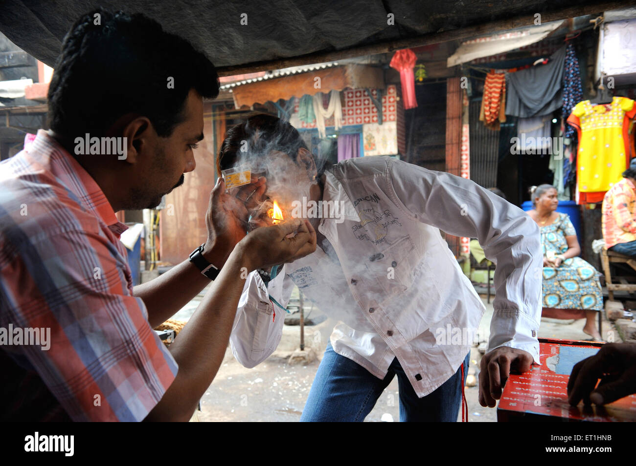 Drug addict smoking  in kamathipura ; Bombay Mumbai ; Maharashtra ; India NO MR - Stock Image