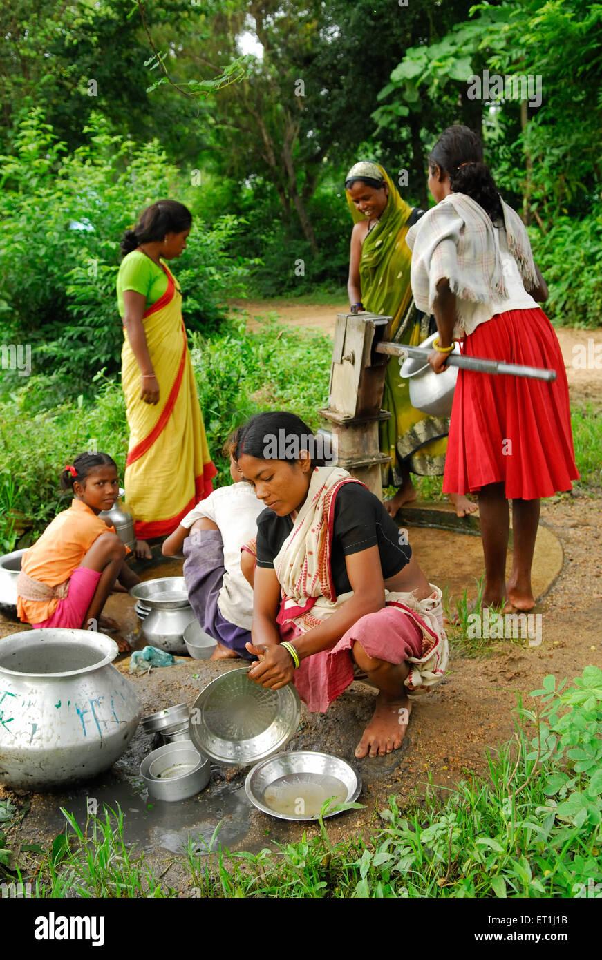Ho tribes women washing utensils around ; Chakradharpur ; Jharkhand ; India NO MR - Stock Image