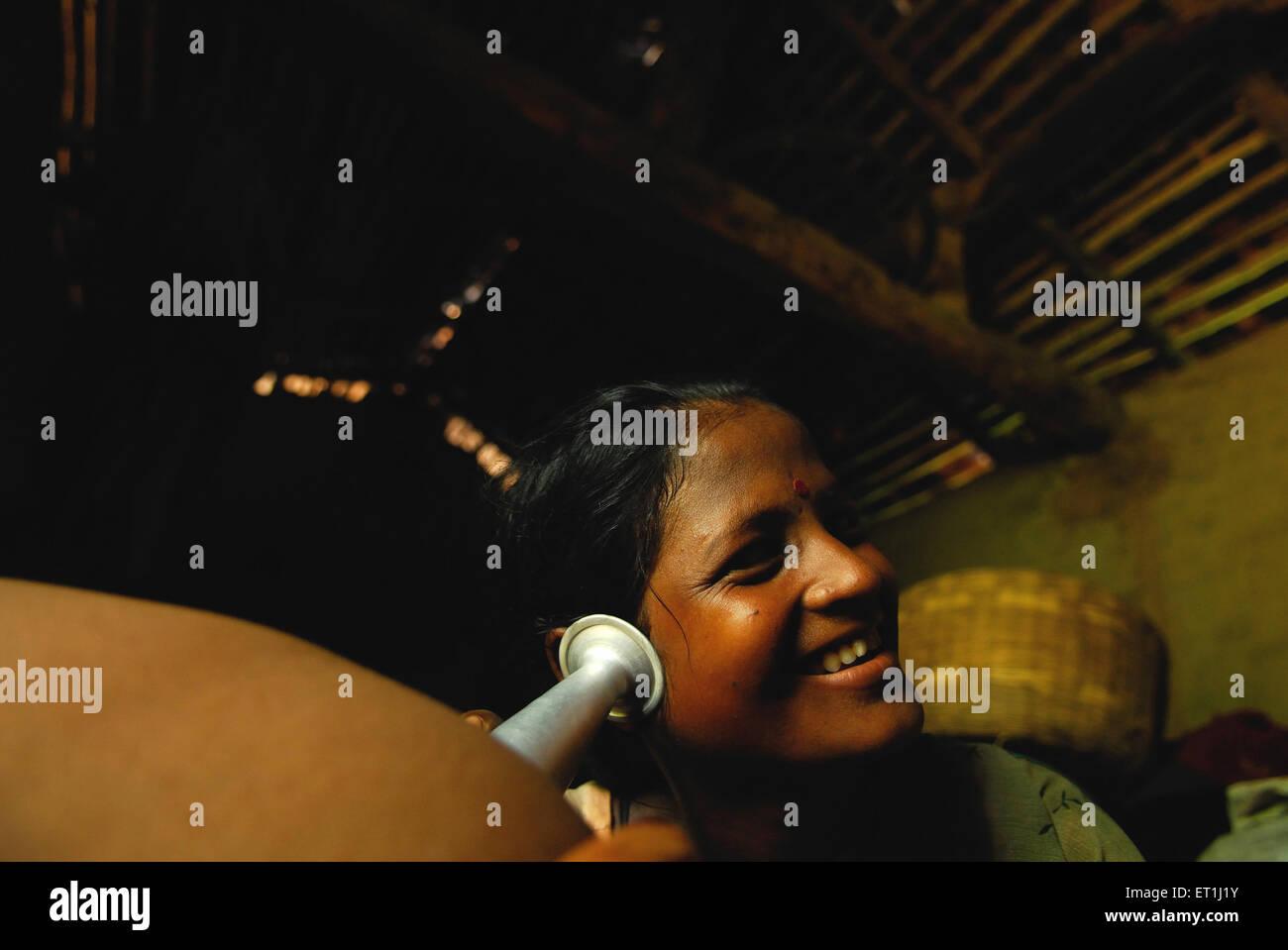 Ho tribes woman trying to listen movement of foetus ; Chakradharpur ; Jharkhand ; India NO MR - Stock Image