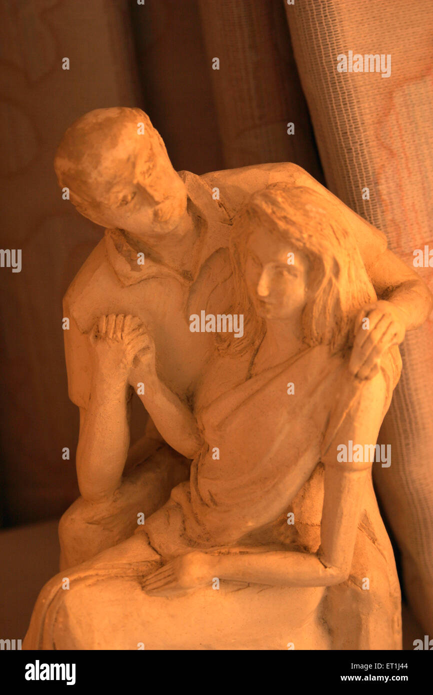 Sunbeam on statue of couple in romantic pose sculpted with plaster of paris ; Pune ; Maharashtra ; India - Stock Image