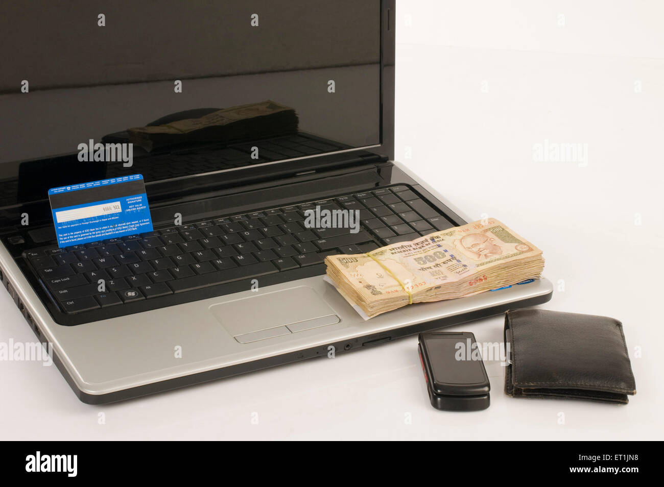 Laptop with credit card and five hundred Rupee notes Pune Maharashtra India Asia June 2011 - Stock Image