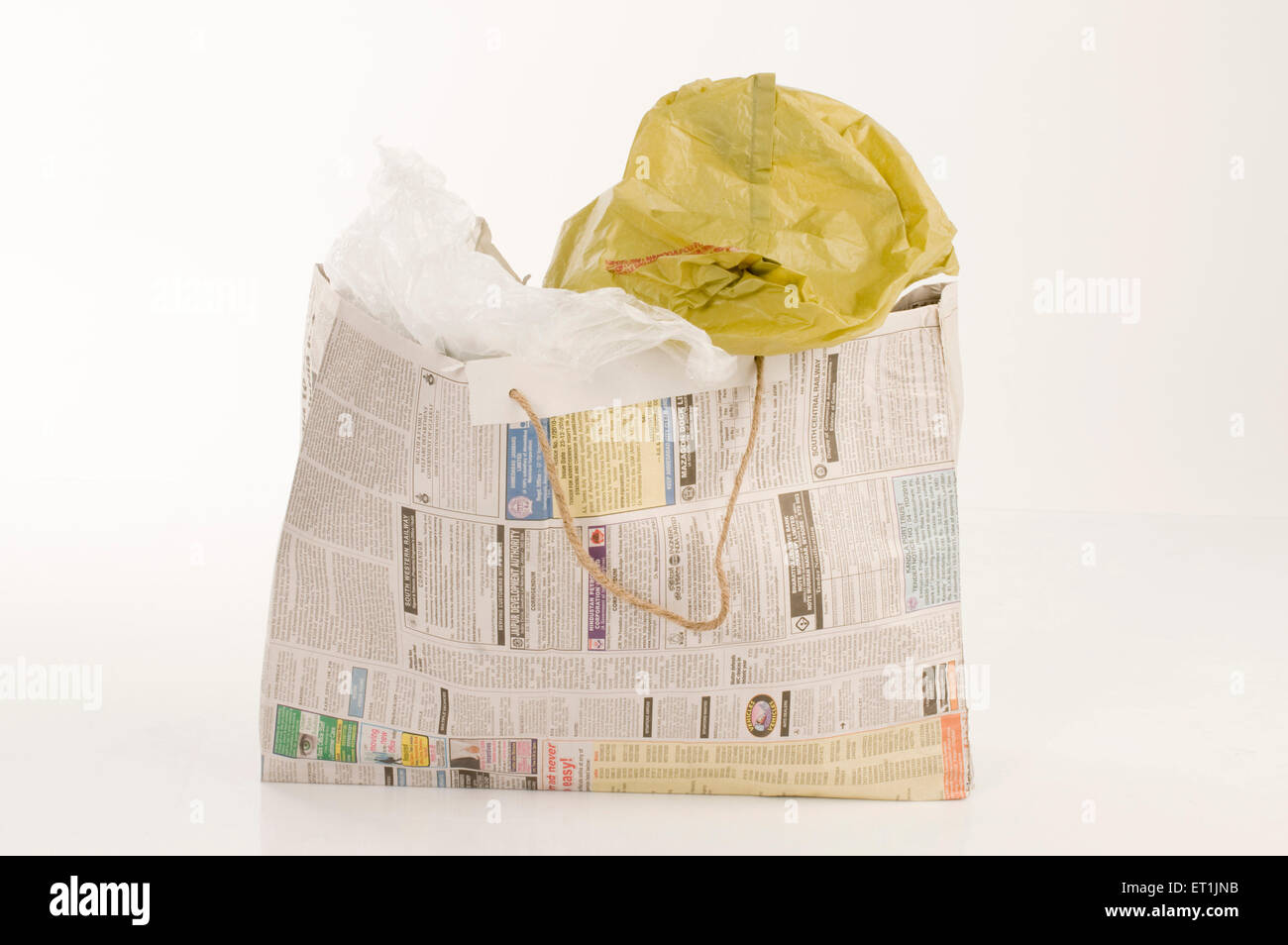 Crumpled plastic bags in newspaper bag Pune Maharashtra India Asia June 2011 - Stock Image