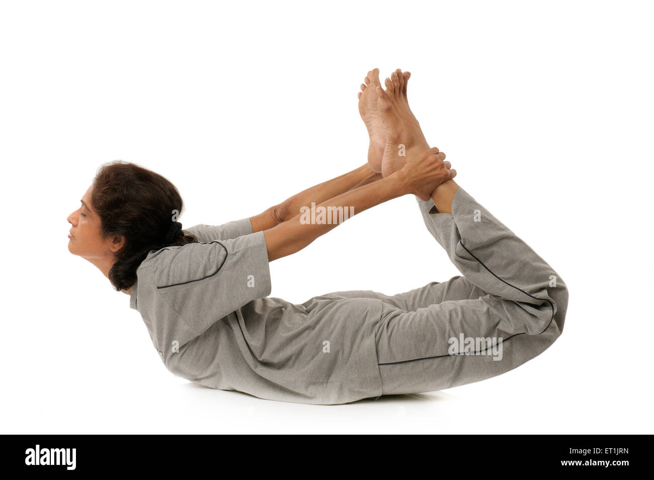 Lady doing yogic exercises dhanura asana MR#190 5 September 2009 - Stock Image