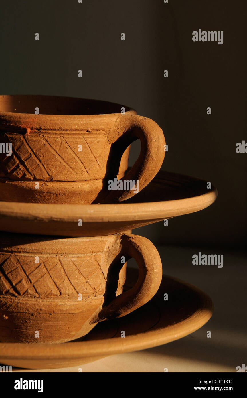 Earthen cups and saucers against black background 25 November 2009 - Stock Image