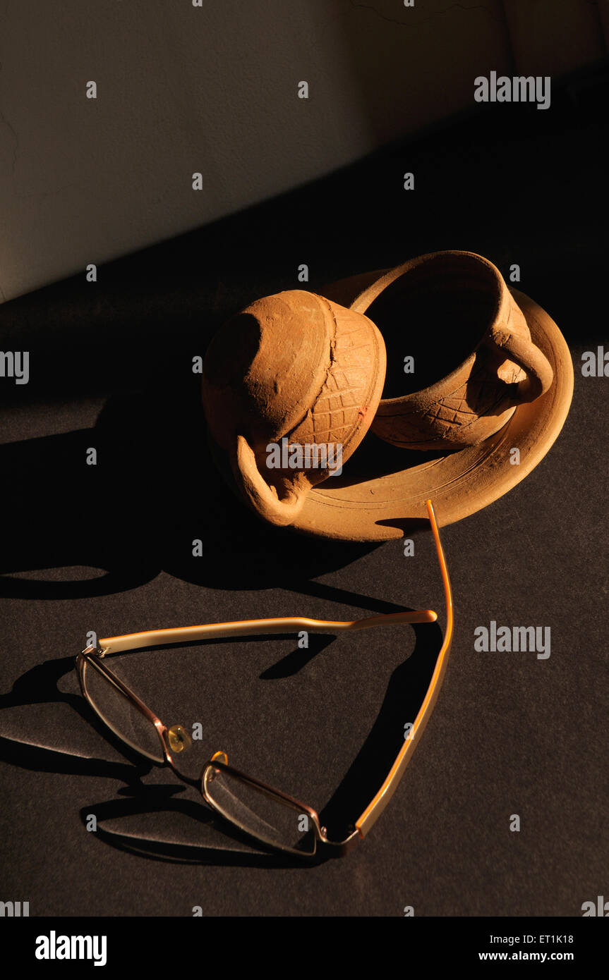 Earthen cups and saucers with spectacles on black background 25 November 2009 - Stock Image