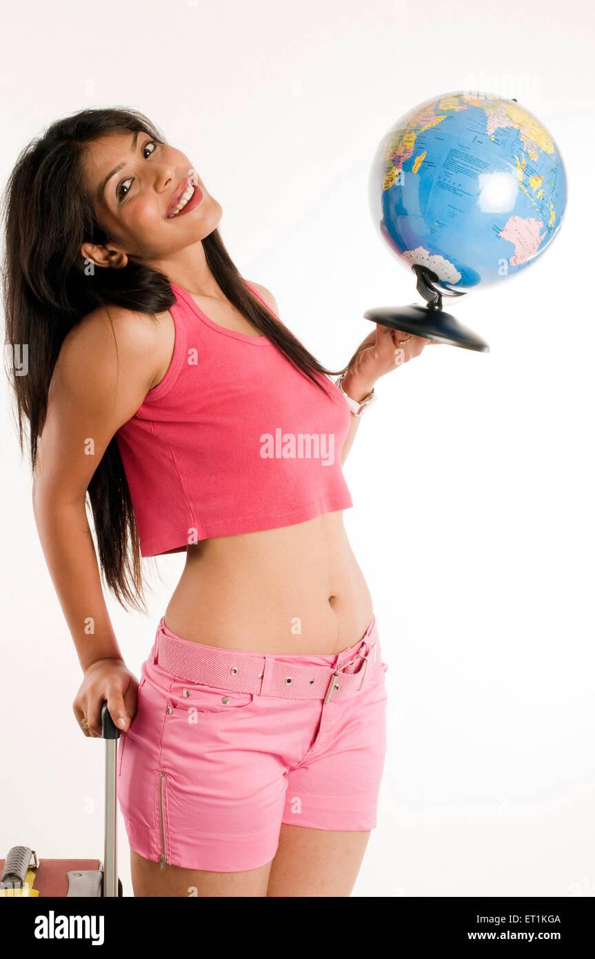 girl wearing sleeveless top and short and holding globe Pune Maharashtra India Asia MR#686Z - Stock Image