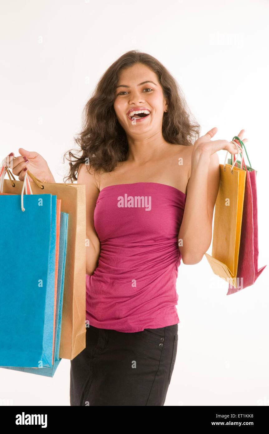 Girl laughingly holding shopping bags Pune Maharashtra India Asia April 2011MR#686 M - Stock Image