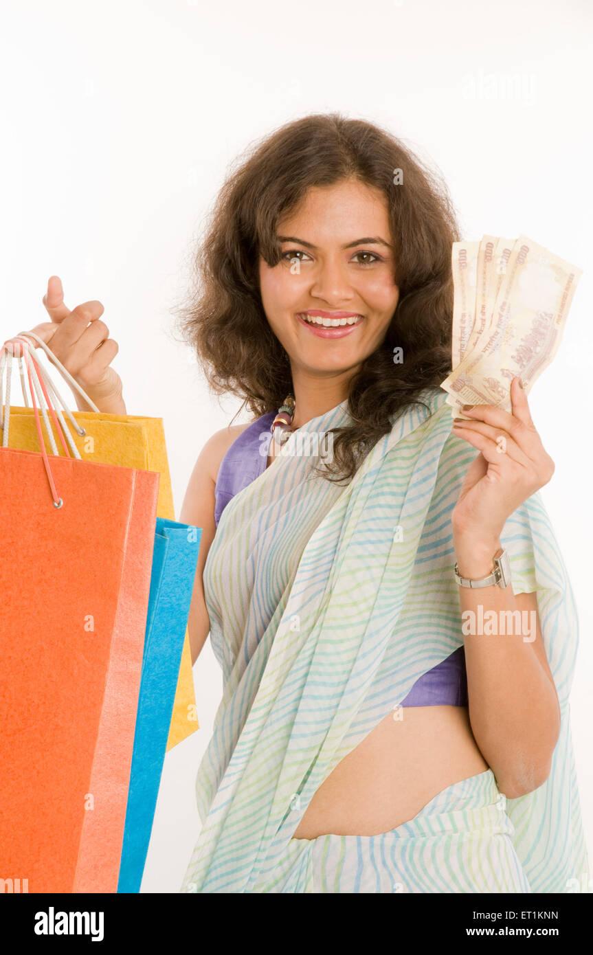 Girl holding shopping bags and Five Hundred notes Pune Maharashtra India Asia MR#686 M June 2011 - Stock Image