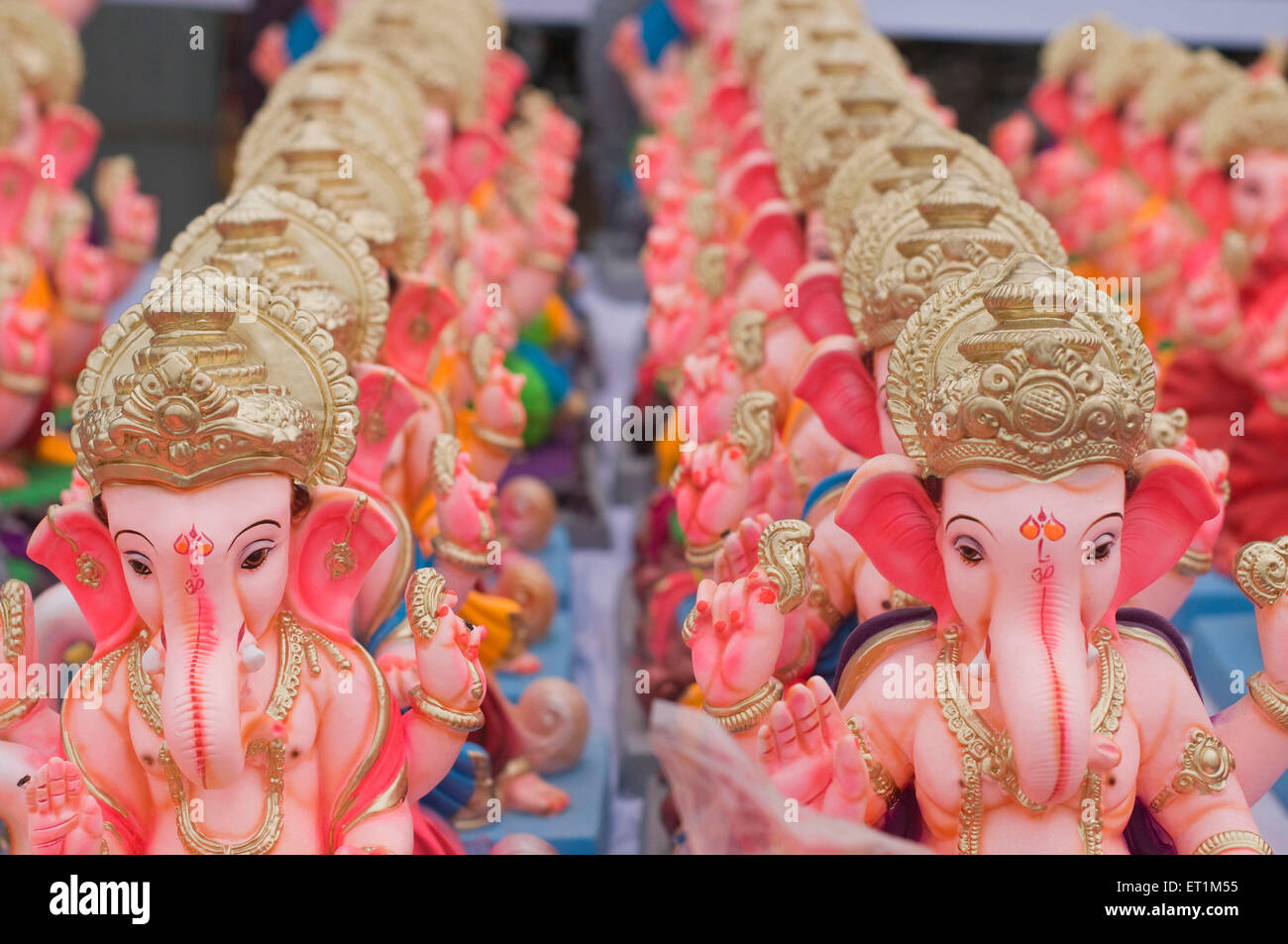 Several small idols of lord Ganesha line up for sale Pune Maharashtra India Asia - Stock Image