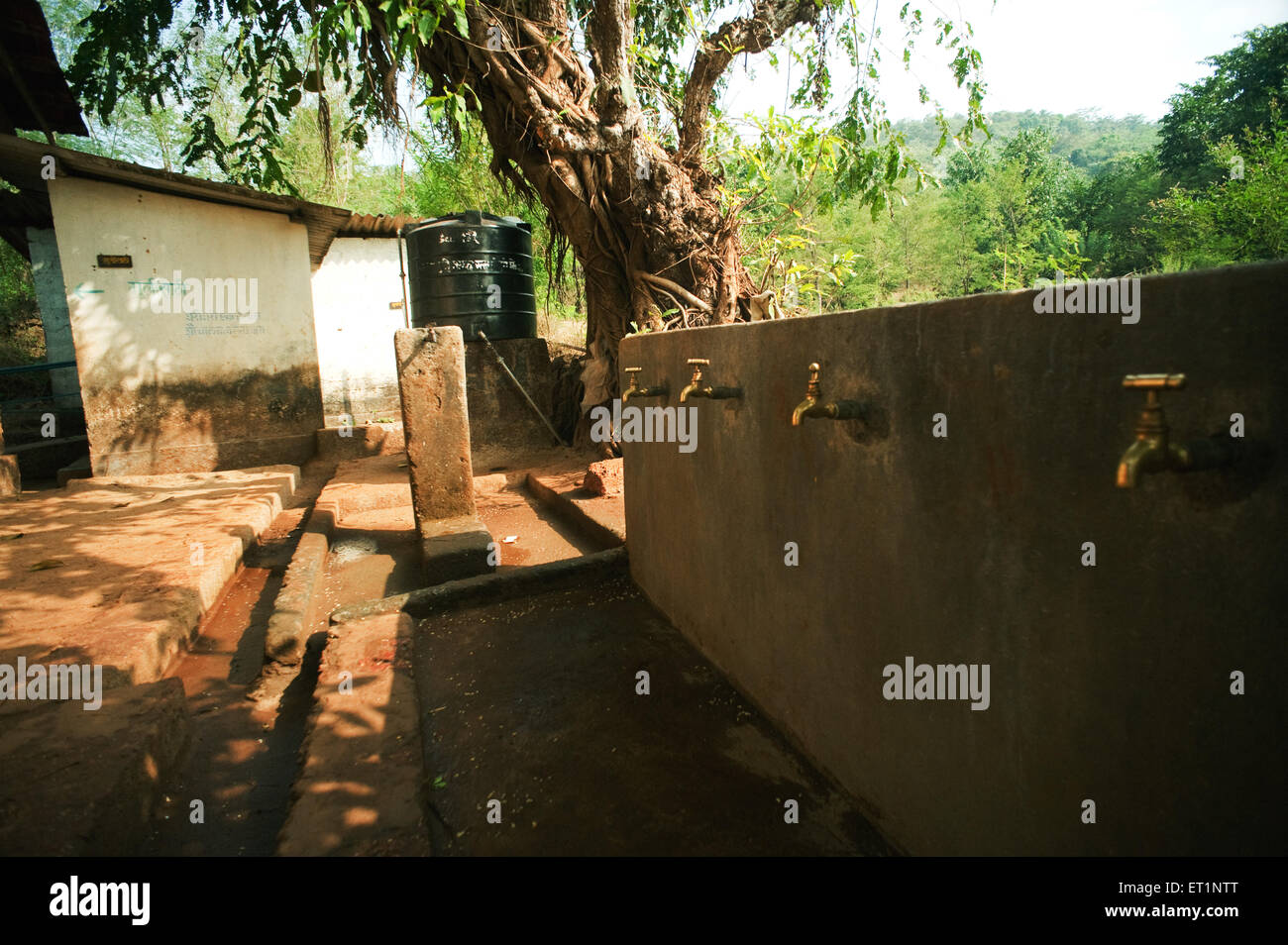 Village school and water tap at Rajwadi ; Sangmeshwar ; Ratnagiri ; Maharashtra  ; India - Stock Image