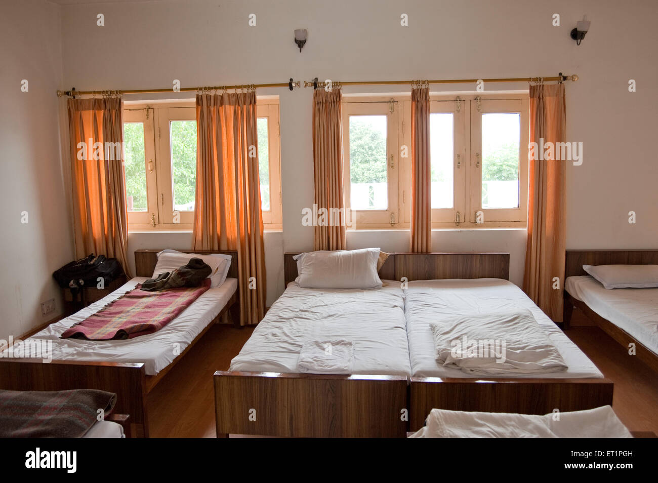 Row of beds in dormitory at sitlakhet hotel in uttarakhand India Asia - Stock Image