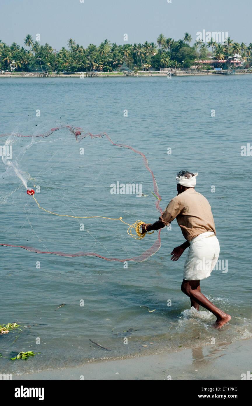 Fisherman casting nets ; Cochin Kochi ; Kerala ; India - Stock Image