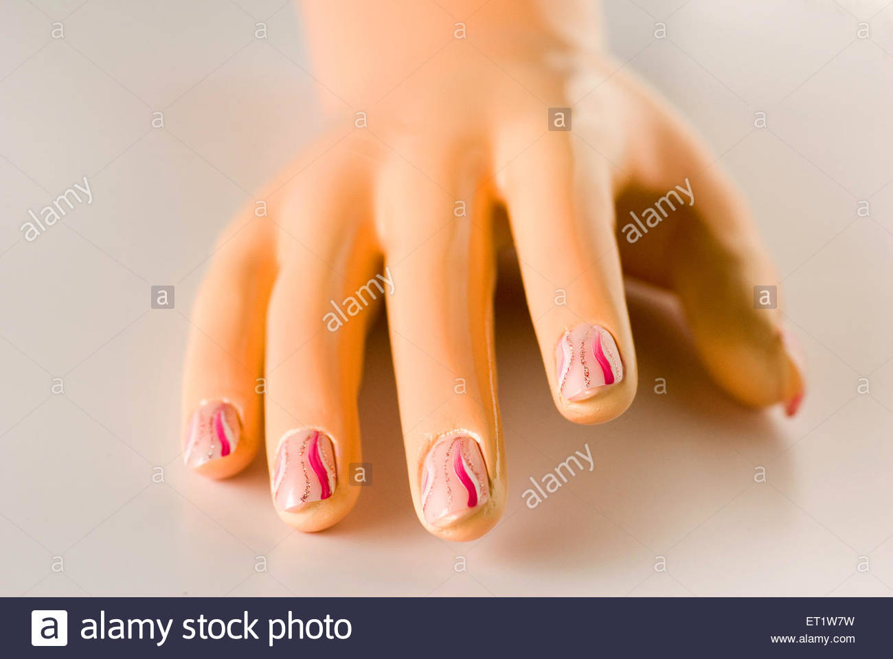 One mannequin hand showing acrylic painted design on nails on white ...