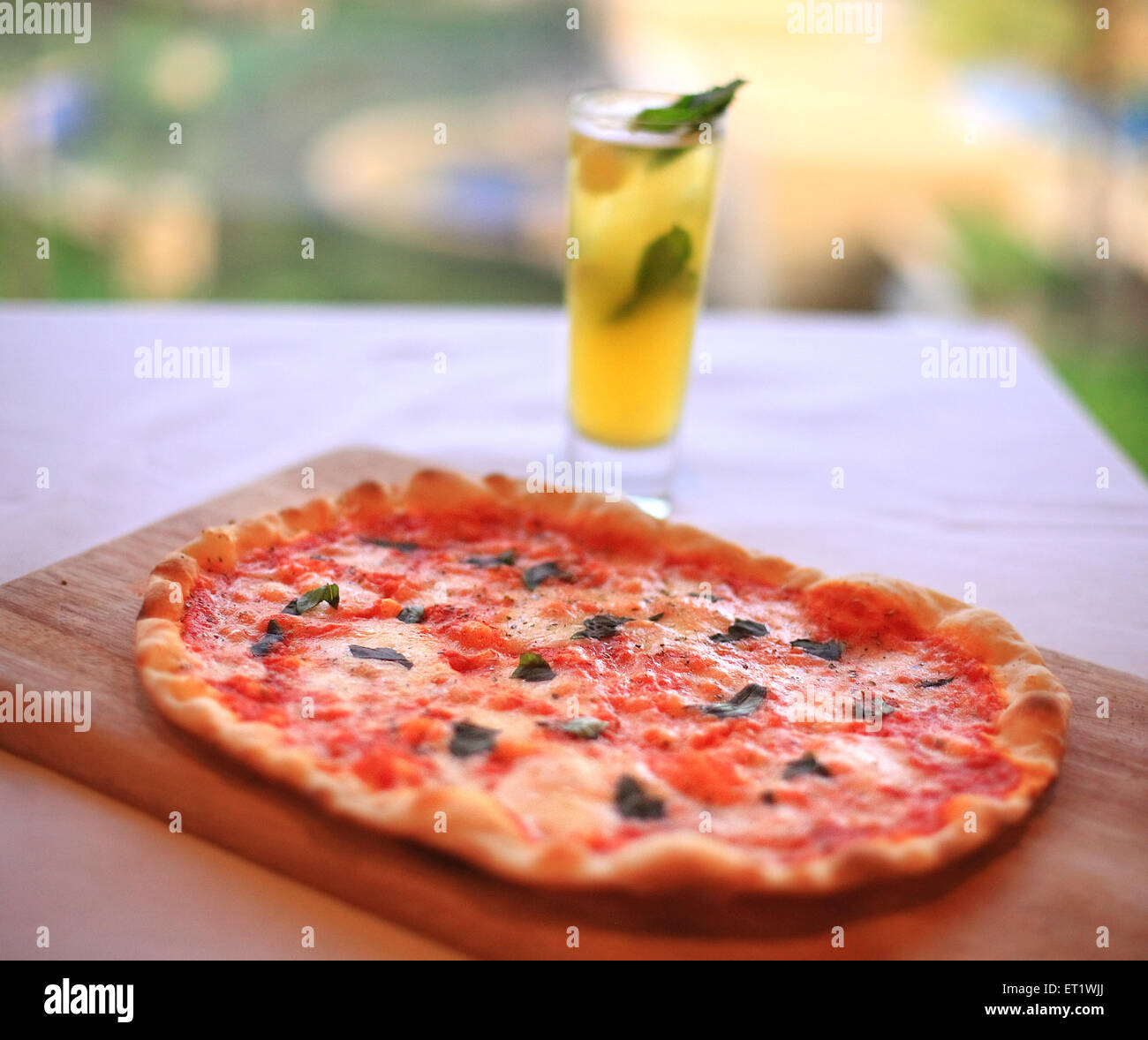Gin based cool drink in glass with pizza on dining table in hotel ; Bombay Mumbai ; Maharashtra ; India - Stock Image
