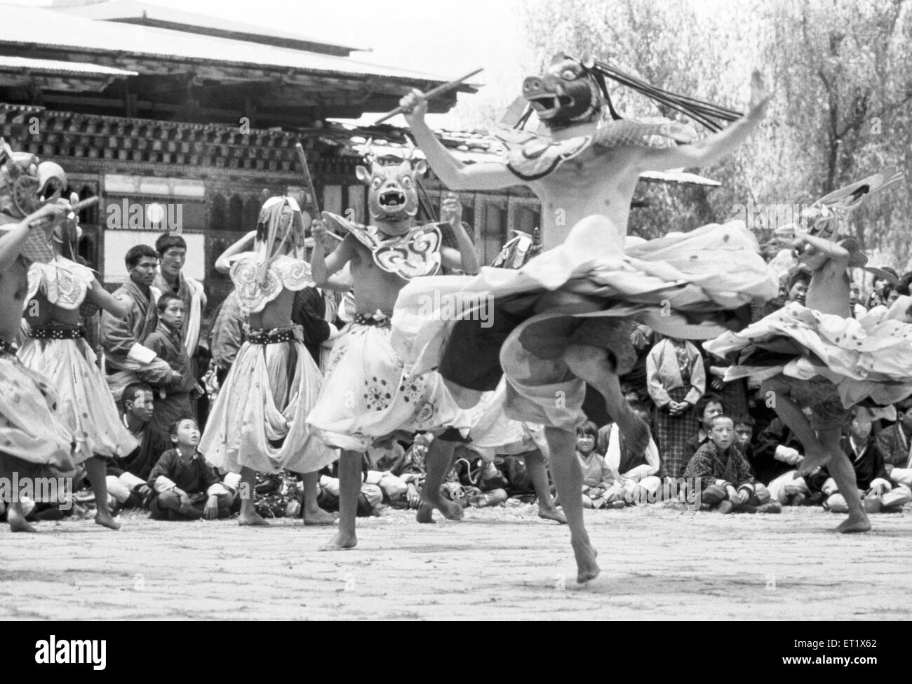 Dancer in full regalia performs at the Thetchu festival in the courtyard of the Dzong at Paro ; Bhutan - Stock Image