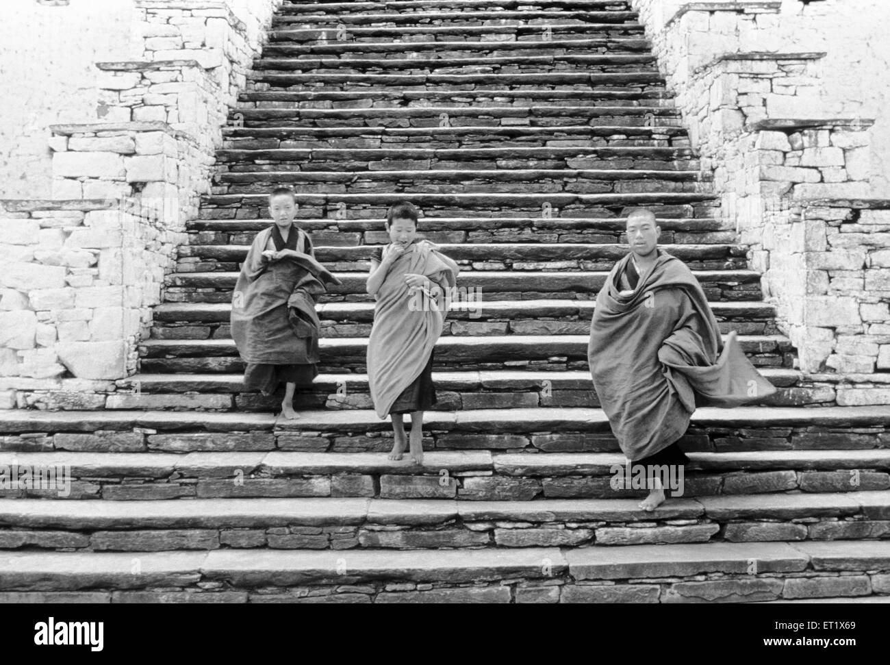 Young monks come down the steps of the ancient Dzong ; monastery at Paro ; Bhutan - Stock Image