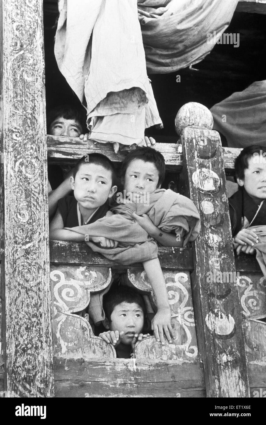 Young monks peep out a window in the monastery at Paro to look at dancers ; Bhutan - Stock Image