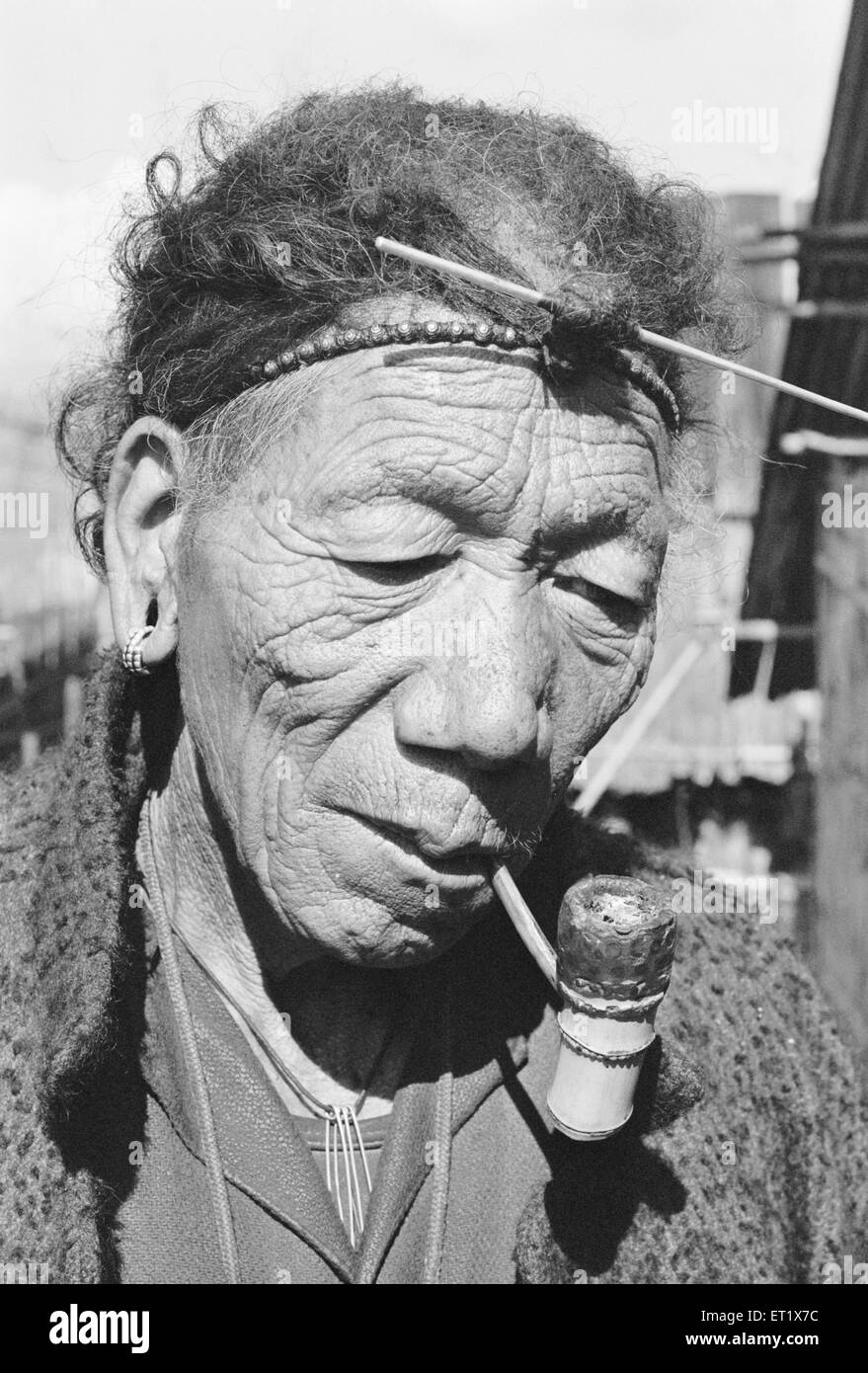 Member of Apa Tani tribe enjoys pipe smoking Ziro District headquarters of Lower Subansiri ; Arunachal Pradesh - Stock Image