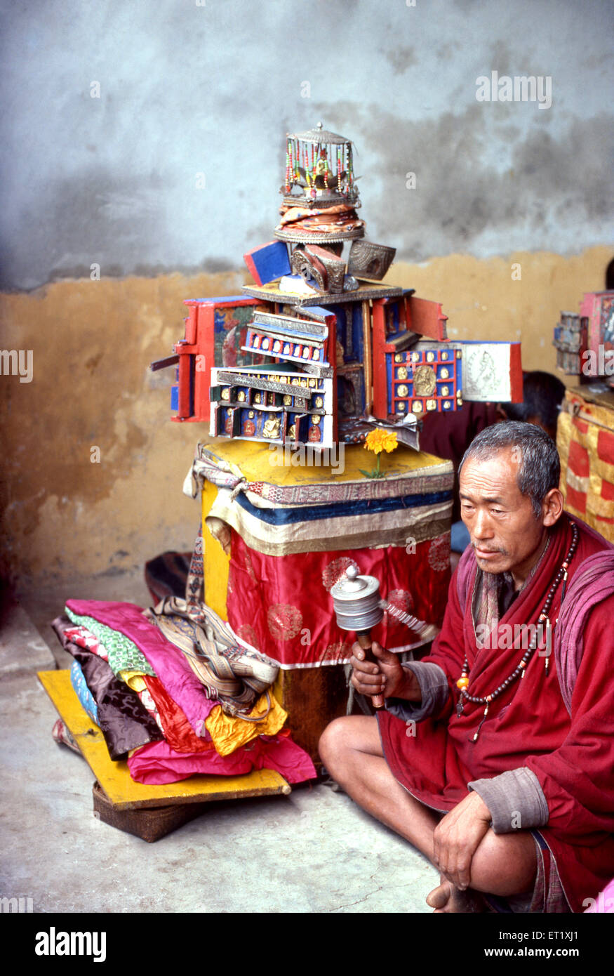 Bhutanese priest with temple of  buddha rotates prayer wheel in Bhutan 1980 NO MR - Stock Image