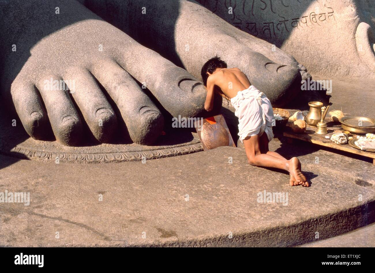 Pilgrim prostrates giant feet of gomateshwara statue at Sravanabelagola ; Karnataka ; India 1980 colossus - Stock Image