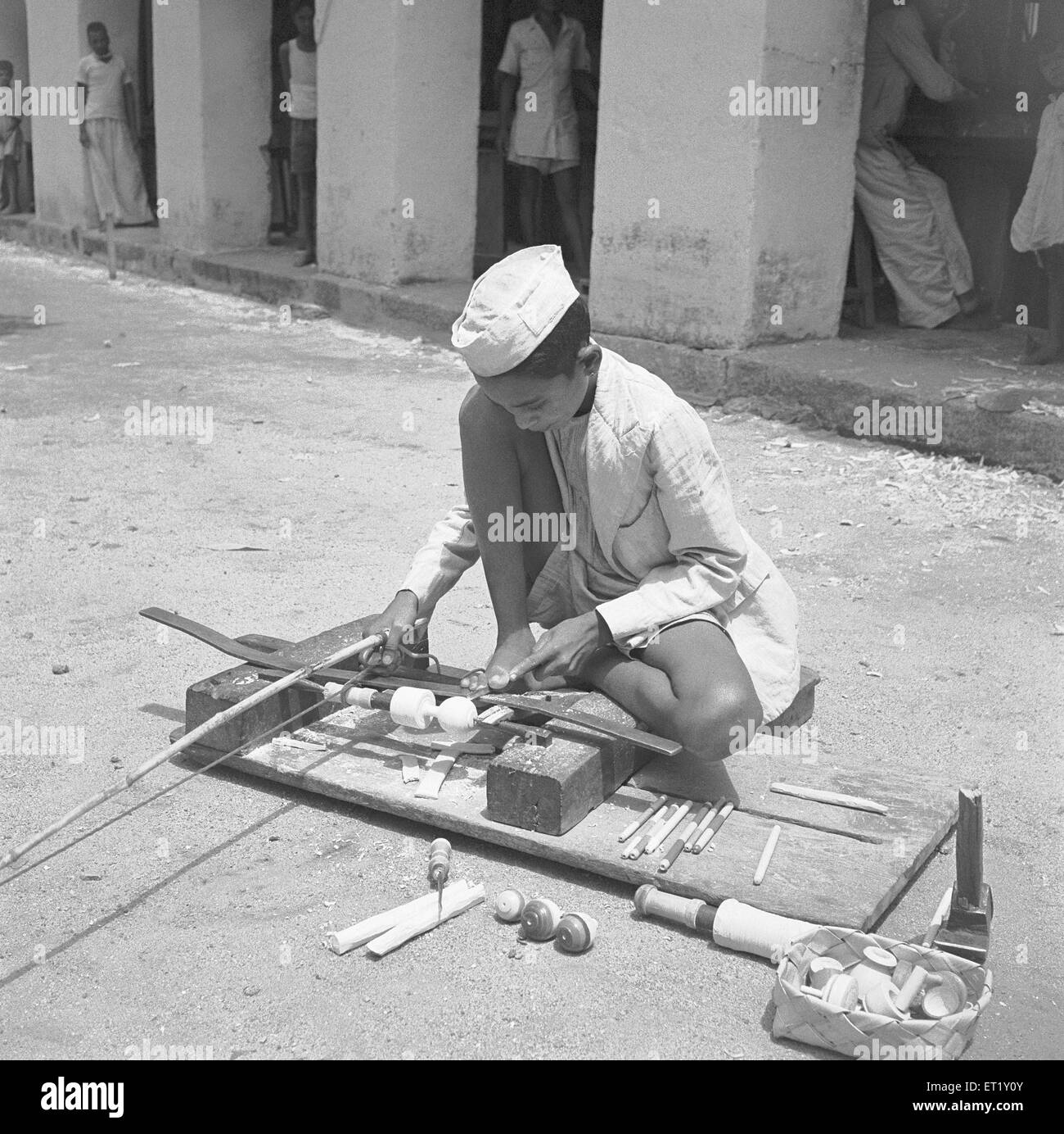 Young boy using portable rotating lathe applying lacquer wringtinforia wood ; painting lacquer toys ; Channapatna - Stock Image