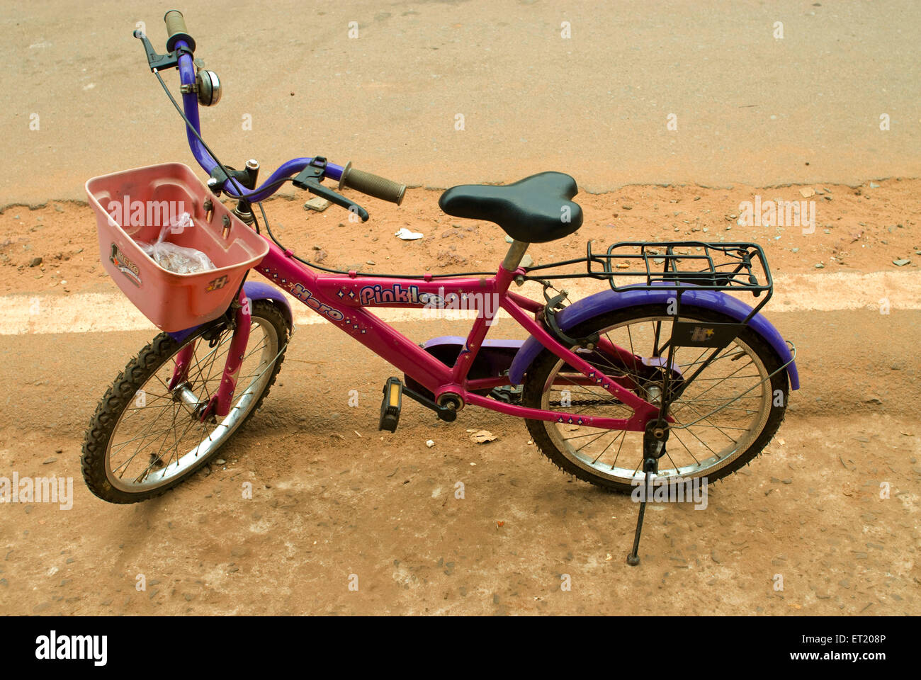 Bicycle parked on road ; Goa ; India - Stock Image