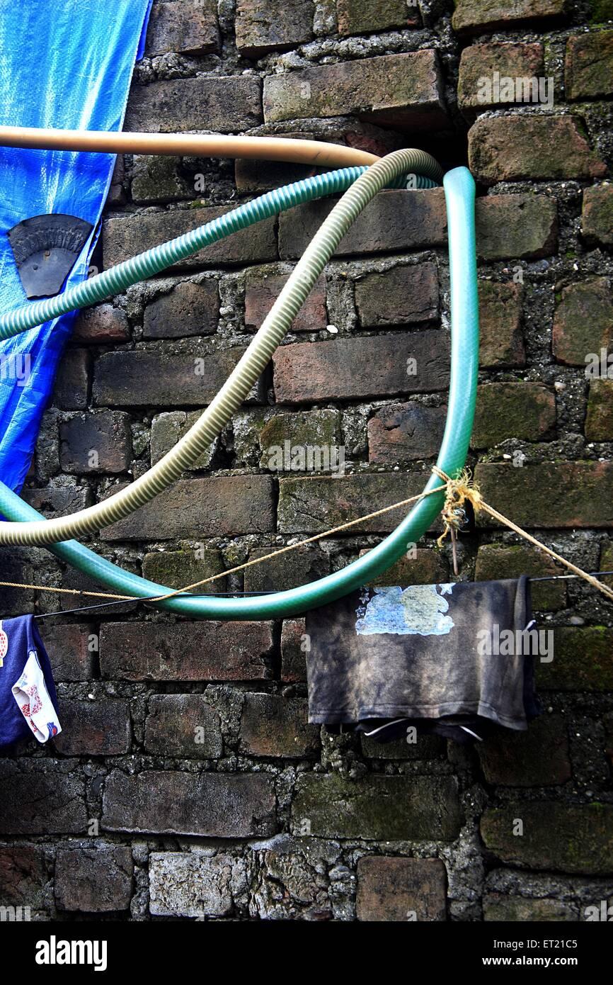 Illegal water pipe in brick wall ; Nirankar Nagar ; Malvani ; Malad ; Bombay Mumbai ; Maharashtra ; India 25 August - Stock Image