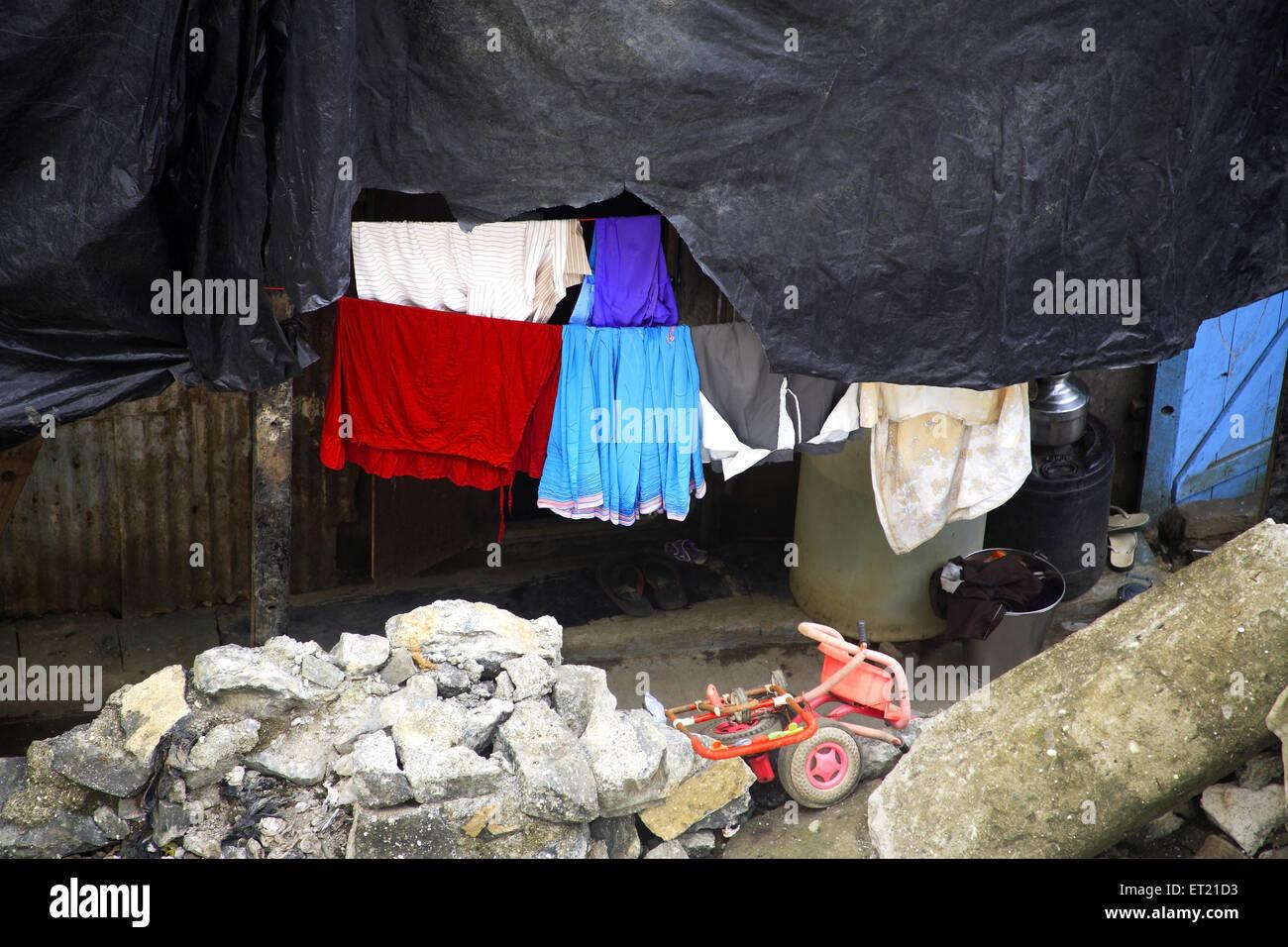 Plastic sheet drying cloth and debris in slum ; Behram Naupada ; Anant Kanekar Marg ; Bandra ; Bombay Mumbai ; Maharashtra Stock Photo