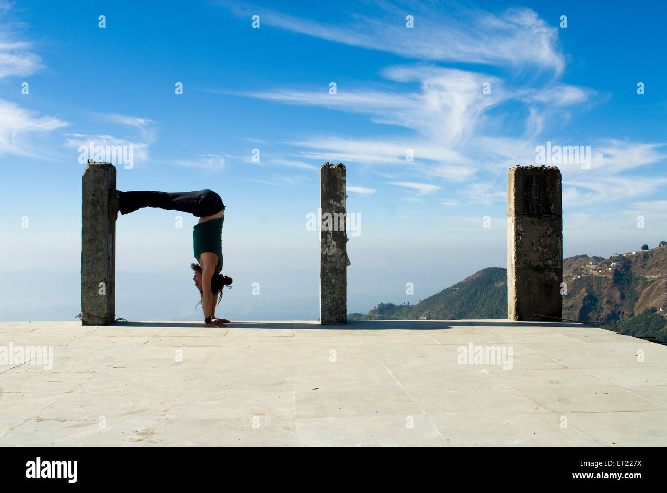 French acrobat doing perfect square in sync with  pillar by bending waist  in Mussoorie ; Dehra Dun ; Uttaranchal - Stock Image