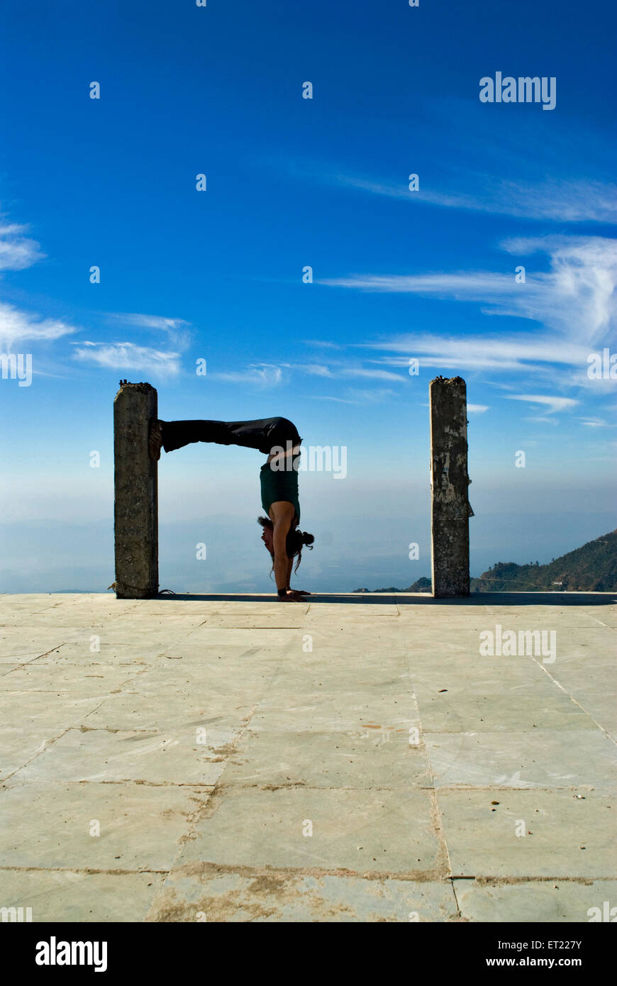 French acrobat doing perfect square in sync with  pillar by bending waist at  Mussoorie ; Dehra Dun ; Uttaranchal - Stock Image
