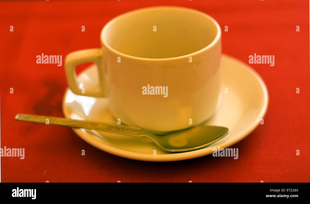 Empty white tea cup with saucer on red table ; Goa ; India - Stock Image