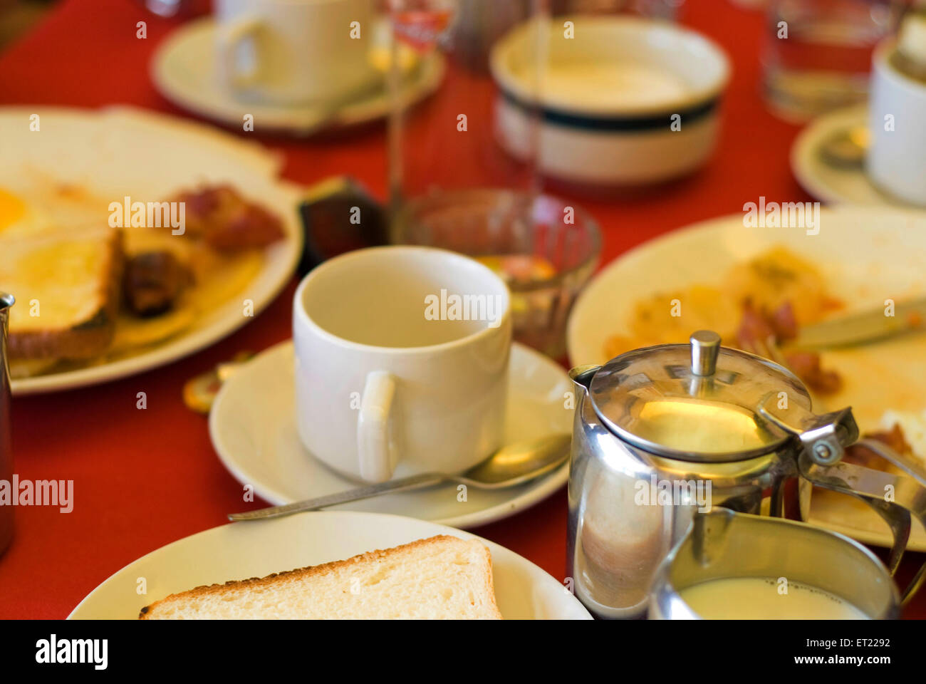 English breakfast laid on red table with tea cups kettles ; Goa ; India - Stock Image