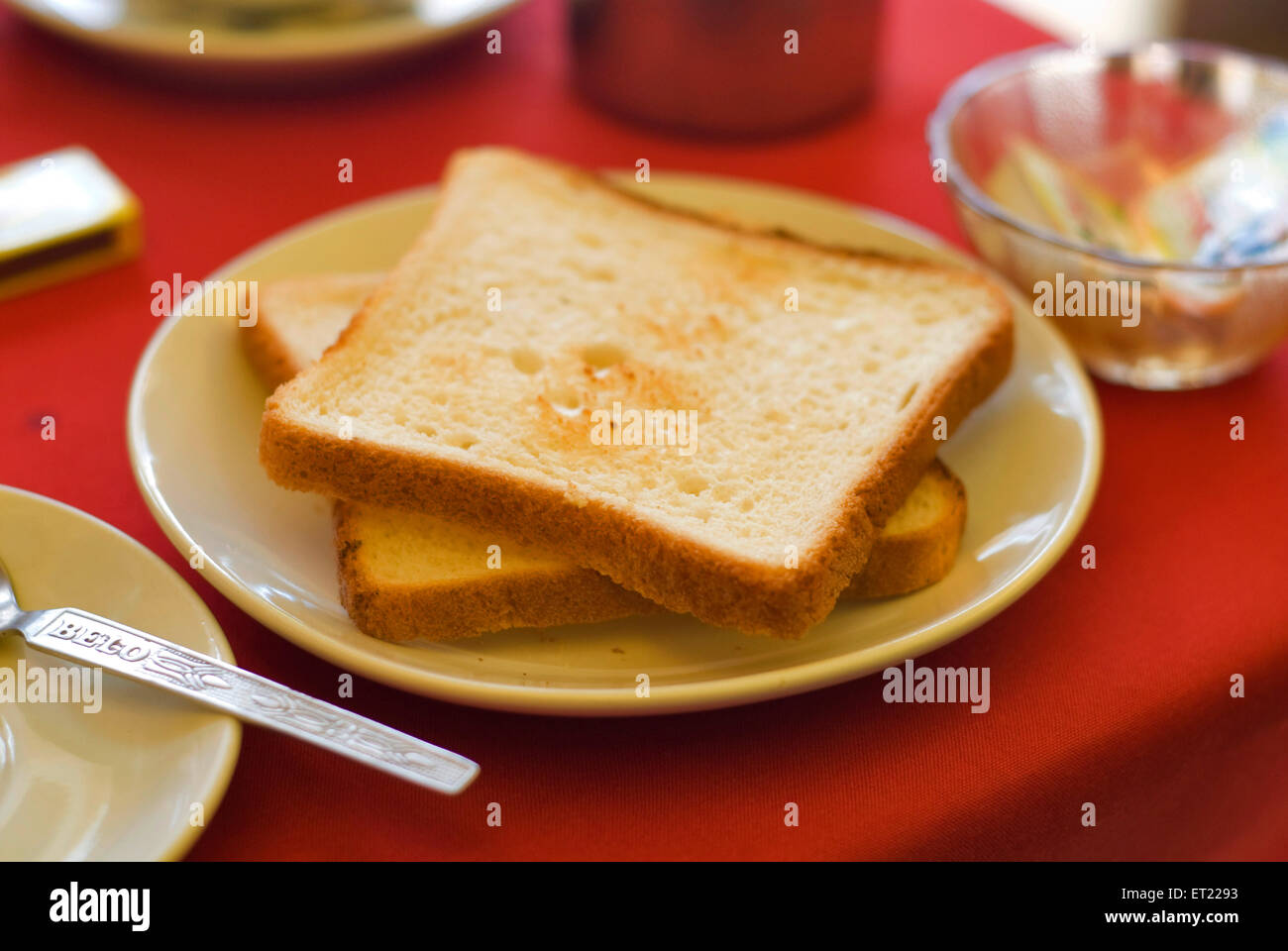 Toasted bread in plate laid on red table ; Goa ; India - Stock Image