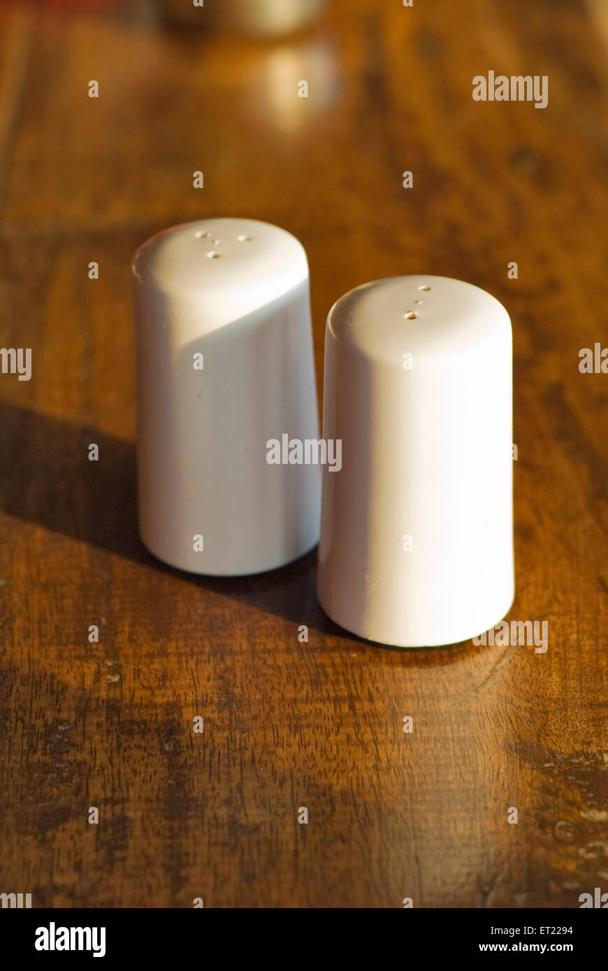 White salt and pepper dispensers on wooden table ; Goa ; India Stock Photo