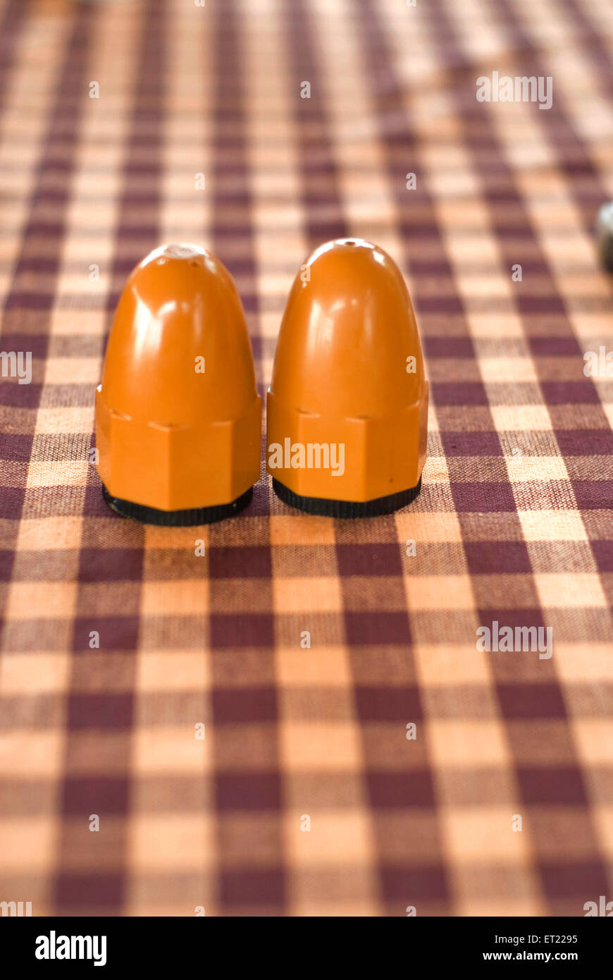 Brown salt and pepper dispensers on checked tablecloth ; Goa ; India - Stock Image
