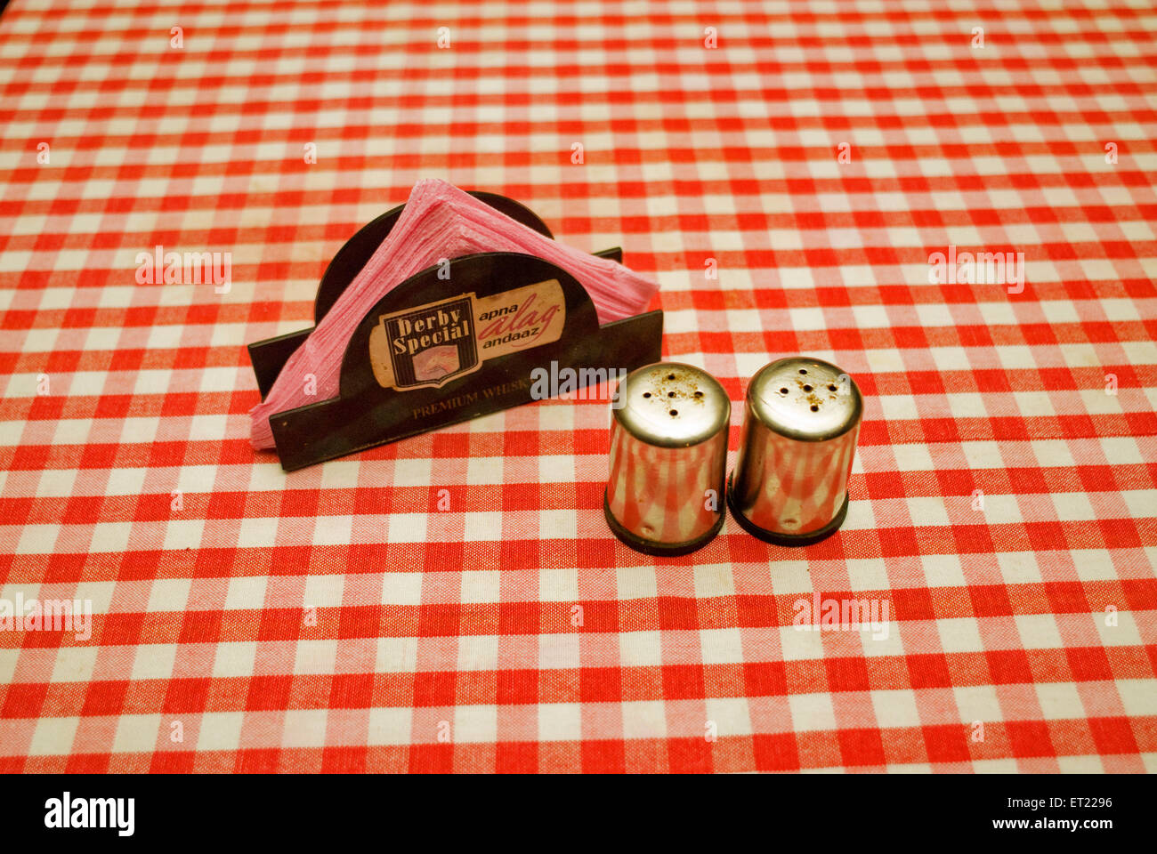 Steel salt and pepper dispensers and paper napkin holder on red and white checked tablecloth ; Goa ; India - Stock Image