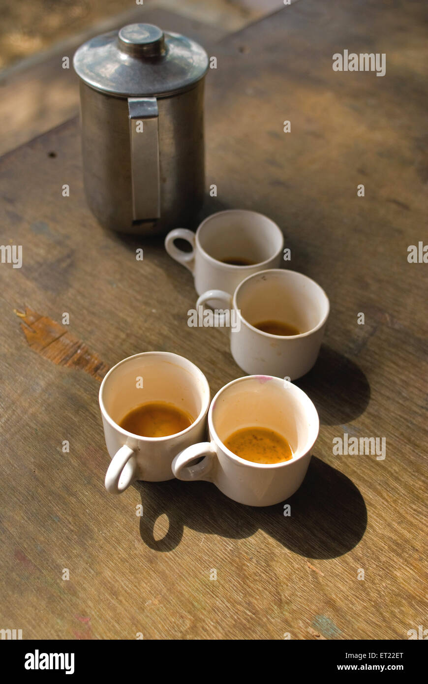 Empty cups of tea and flask on table - Stock Image