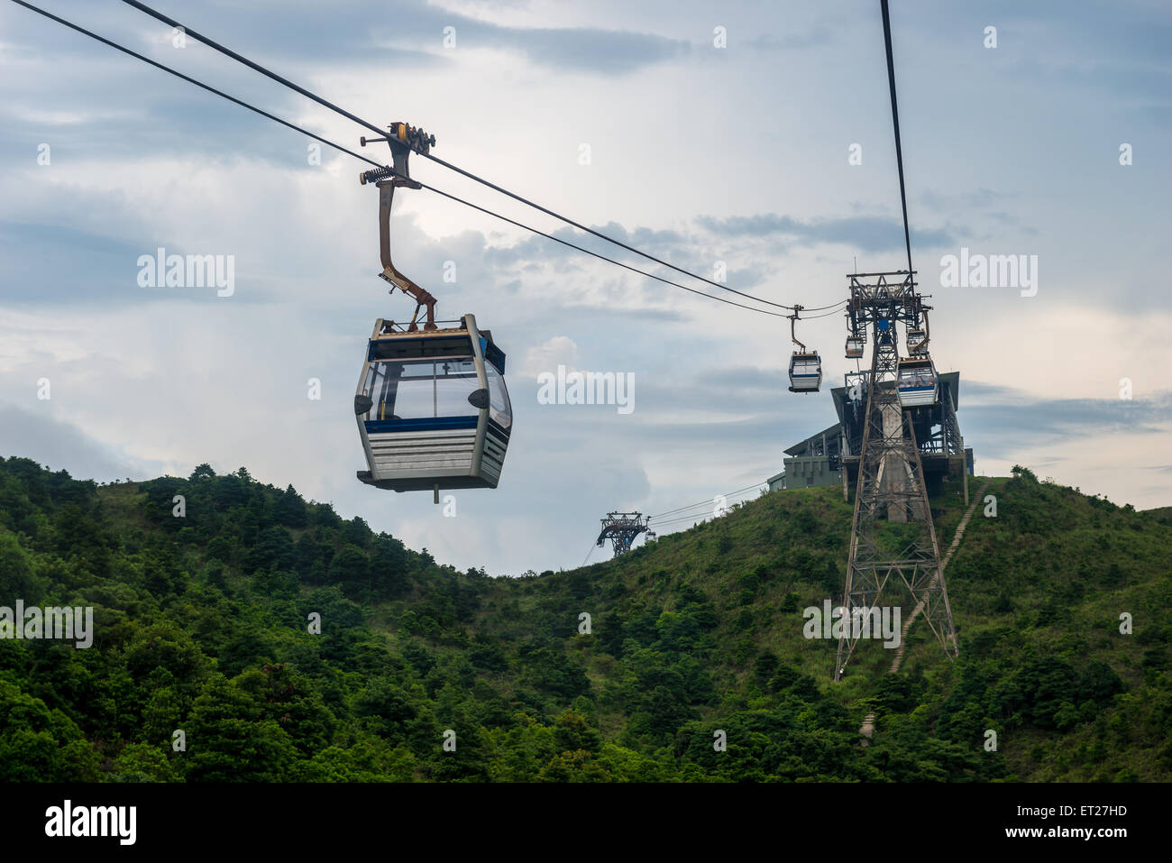 Cable cars rise up over the mountains of Lantau Island in Hong Kong, SAR. - Stock Image