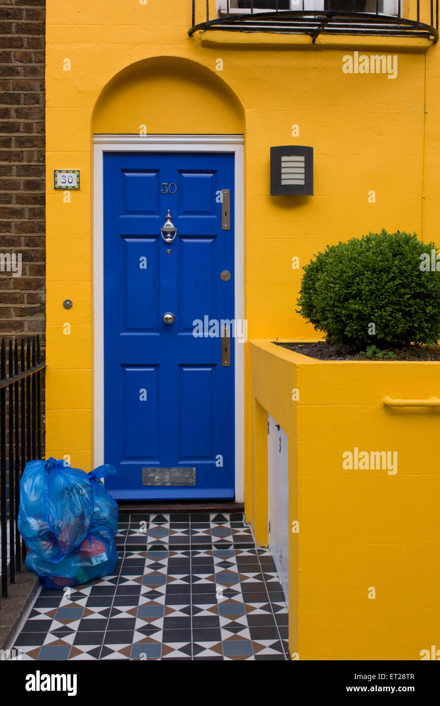 Yellow House With Blue Door And Blue Recycling Bags On