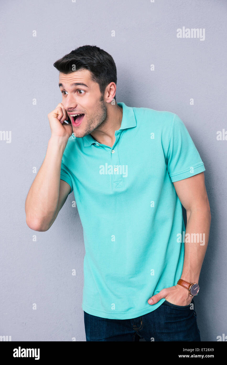 Cheerful young mna talking on the phone over gray background and looking away - Stock Image