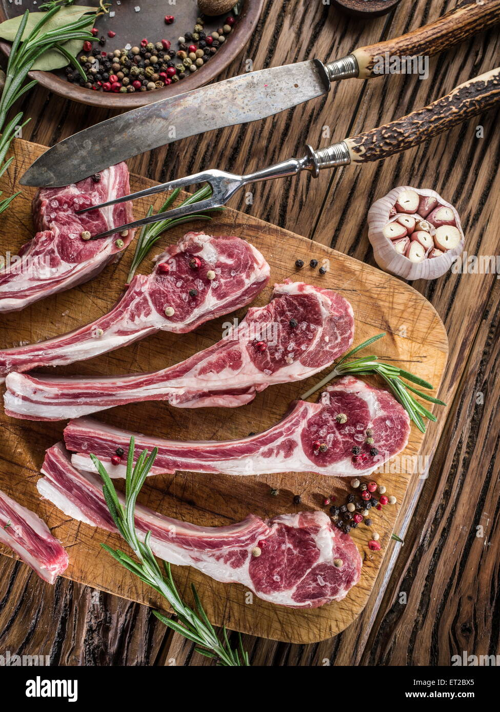 Raw lamb chops with garlic and herbs on the old wooden table. - Stock Image